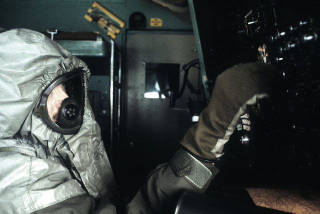 A flight crewman in protective clothing works in the cockpit of a C-141 Starlifter aircraft during a chemical warfare exercise