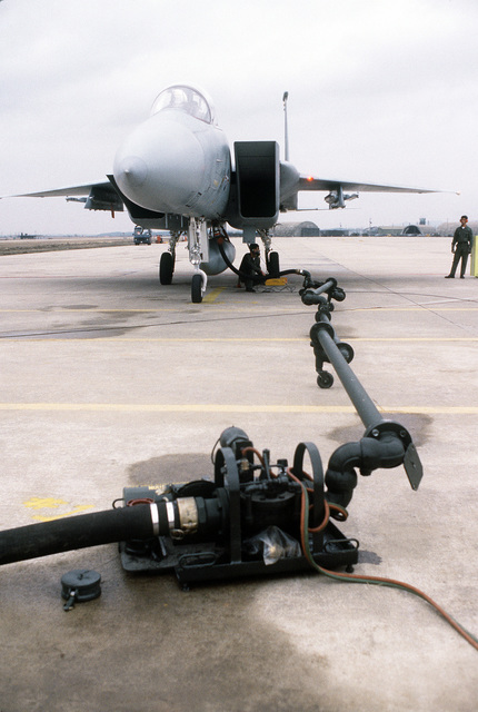 A front view of an F-15 Eagle aircraft being refueled from a fuel bladder pit. The aircraft, from the 18th Tactical Fighter Wing, is involved in exercise Team Spirit '81