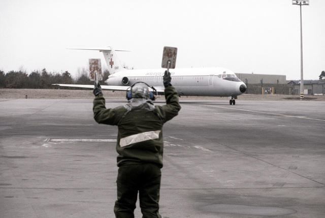 """A ground crewman in protective clothing directs a C-9 Nightingale aircraft into parking position during a chemical warfare exercise. """"Patients"""" will be downloaded from the C-9 aircraft and loaded onto a C-141 Starlifter aircraft"""