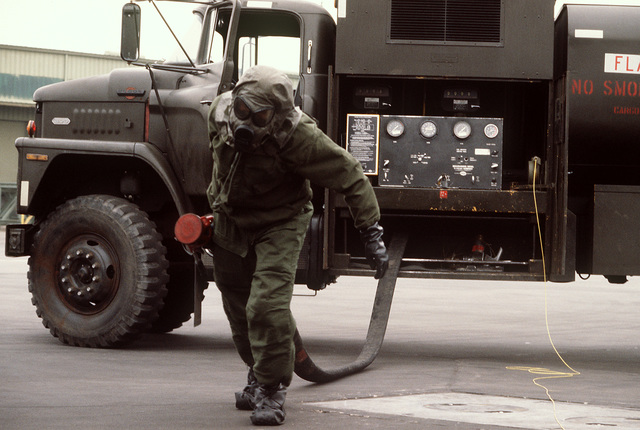 A ground crewman wearing protective clothing for a chemical warfare exercise drags a fuel hose towards a C-141 Starlifter aircraft