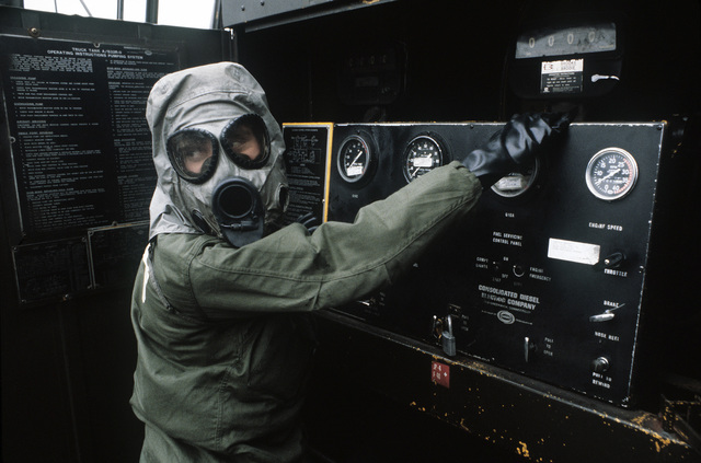 A ground crewman wearing protective clothing for a chemical warfare exercise monitors the controls of a tank while a C-141 Starlifter aircraft is being refueled
