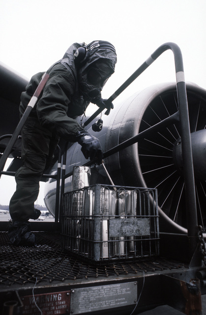 A ground crewman wearing protective clothing performs postflight maintenance on a C-141 Starlifter aircraft during a chemical warfare exercise