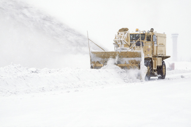 A left front view of a large snow blowing truck from the 21st Civil Engineering Squadron, Roads and Grounds Section, clearing snow and ice off the main runway