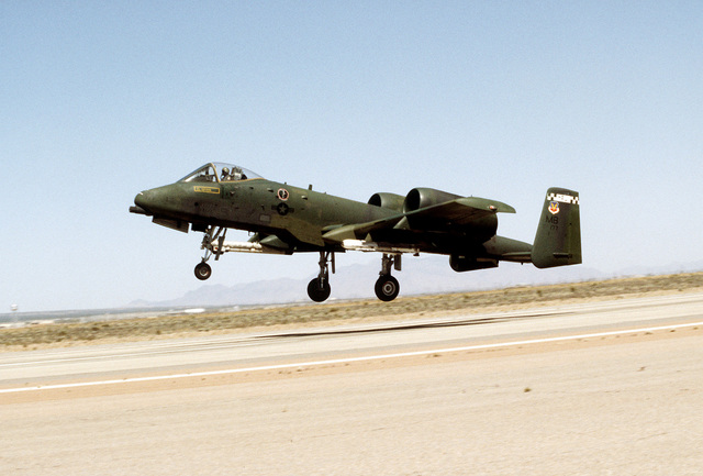 A left side view of an A-10A aircraft taking off during exercise Border Star '81. The aircraft is carrying an ALQ-119 electronic countermeasures pod on the right wing and a missile on the left wing