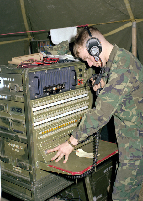 A Marine corporal operates a cordless telephone switchboard SB-3082 (V) 2/GT. The corporal is a part of Marine Aircraft Group 12 (MAG-12) and is participating in exercise Team Spirit '81