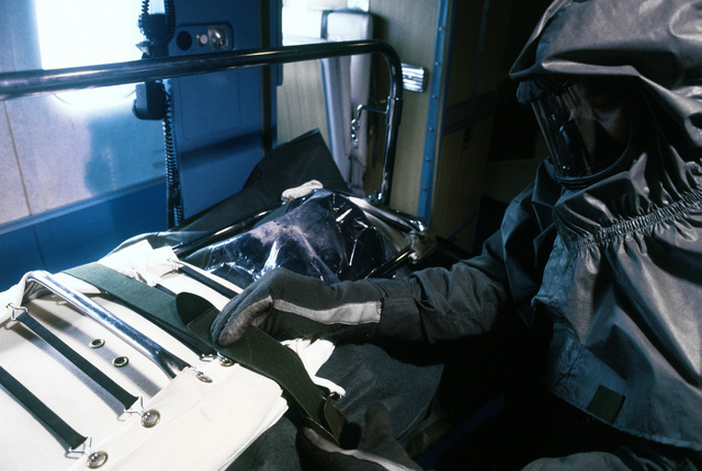 """A medical technician wearing protective clothing works on a """"patient's"""" during a chemical warfare training exercise"""