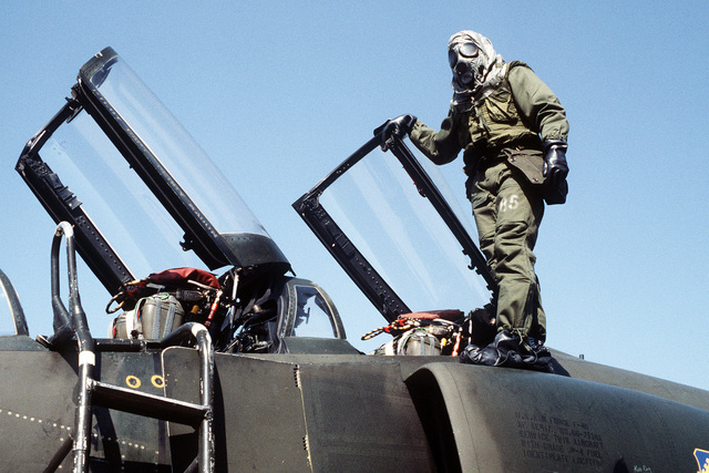 A security policeman in chemical warfare gear stands on an F-4 Phantom II aircraft while guarding a ramp area. The airman is an 8th Security Police Squadron member participating in exercise Team Spirit '81