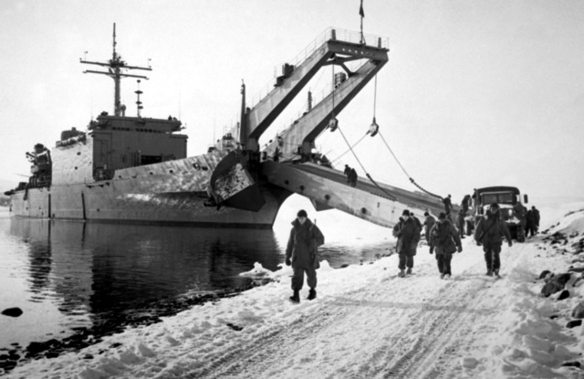 A starboard bow view of the tank landing ship USS BARNSTABLE COUNTY (LST-1197) as troops and vehicles disembark during the NATO exercise Cold Winter (COLDEX-FLOTEX '81). The exercise is intended to test all phases of amphibious operations in sub-freezing weather