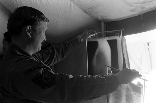 """A technician checks a """"patient's"""" X-ray in the tent city. The technician is assigned to the 657th Tactical Field Hospital Squadron, involved in exercise Team Spirit '81"""
