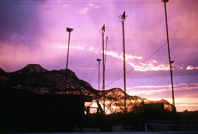 A view of a microwave communications site, under a camouflage net, silhouetted against the horizon at sunset during exercise Border Star '81