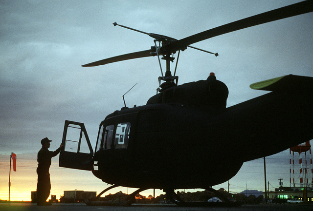 A view of a soldier and an Army UH-1 Iroquois helicopter silhouetted against the horizon at sunset during exercise Border Star '81