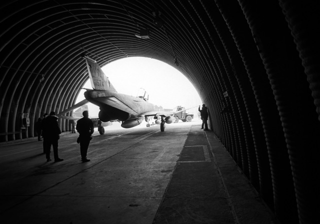 A view of an F-4E Phantom II aircraft being towed out of a shelter for flight. The aircraft is assigned to the 37th Tactical Fighter Wing, involved in exercise Team Spirit '81