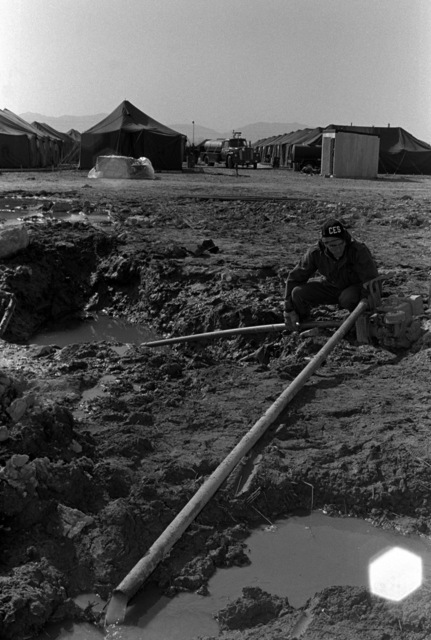 A1C Brumagin pumps water from a ground hole to facilitate repair of a broken main. The airman is a member of the 15 Civil Engineering Squadron, involved in Exercise Team Spirit '81