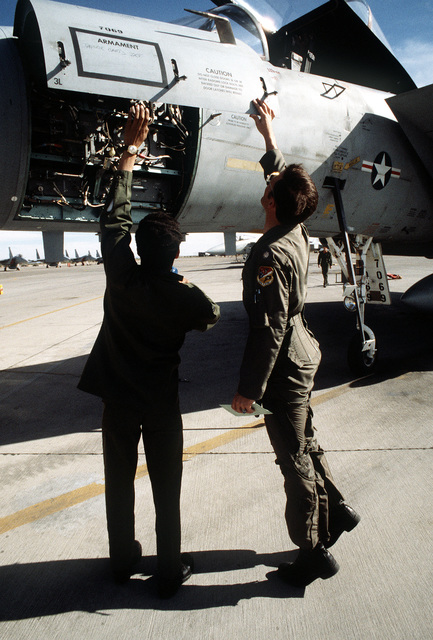 A1C Jeff Sands and MAJ Jim Neu inspect an F-15 Eagle aircraft during exercise Border Star '81