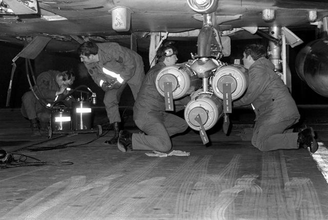 Air Force members load Mark 20 Rockeye bombs on an F-4 Phantom II aircraft