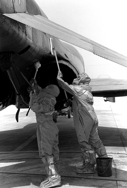 Air Force members, wearing chemical warfare gear, decontaminate a fighter aircraft during base defense training, part of exercise Team Spirit '81