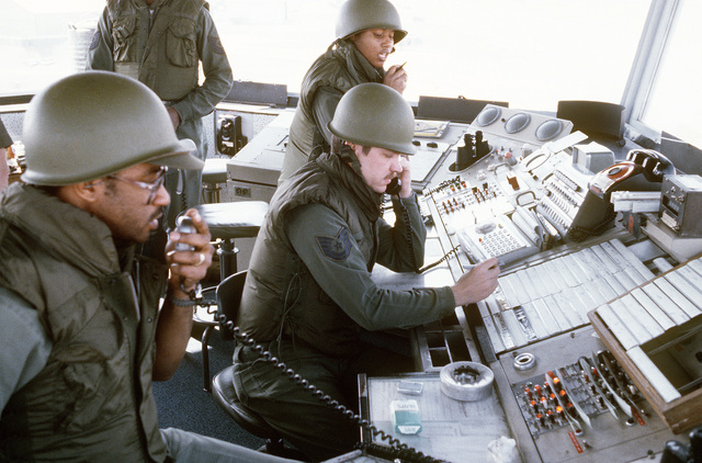 Air traffic controllers, in the control tower, are in contact with incoming and outgoing aircraft. The controllers undergo chemical warfare training during exercise Team Spirit '81