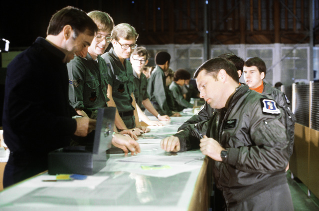 Airmen and noncommissioned officers fill out flight debriefing forms before a C-141 Starlifter aircraft flight during exercise Team Spirit (Coronet Spray)
