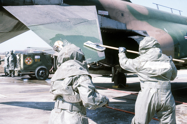 Airmen, clad in chemical warfare gear, perform F-4 Phantom II aircraft decontamination maintenance. The airmen are assigned to the 8th Security Police Squadron, involved in exercise Team Spirit '81