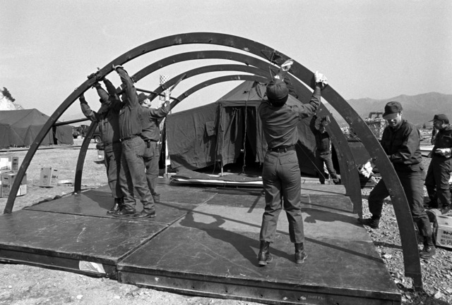 Airmen erect the structure of a dome tent in the tent city for Exercise Team Spirit '81. The airmen are from the 655th Tactical Field Hospital Squadron