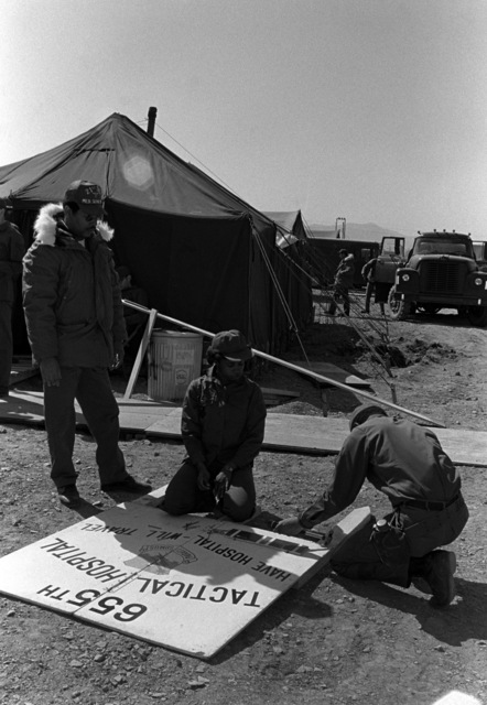 Airmen prepare a squadron sign for set-up in the tent city during Exercise Team Spirit '81. The airmen are from the 655th Tactical Field Hospital Squadron