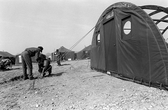 Airmen secure a dome tent with ropes, tied to spikes, in the tent city. The airmen are from the 655th Tactical Field Hospital Squadron, involved in Exercise Team Spirit '81