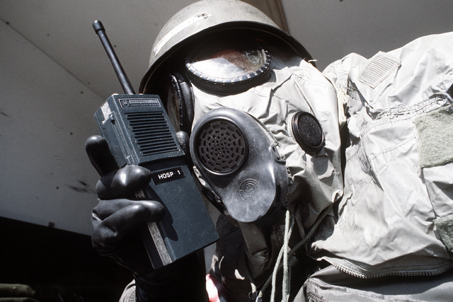 An 8th Combat Support Group preparedness team member wearing chemical warfare gear talks on the radio during exercise Team Spirit '81
