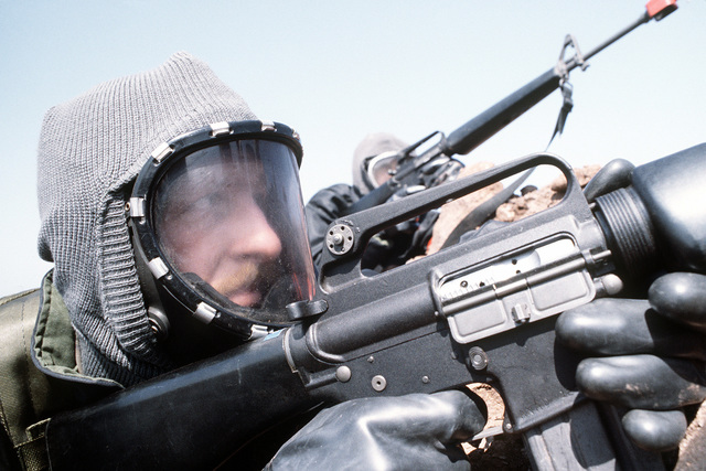 An 8th Security Police Squadron member wearing chemical warfare gear mans an M-16 rifle during exercise Team Spirit '81