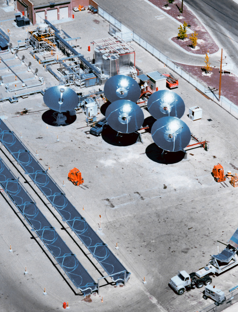 An aerial view of Sandia National Laboratories Midtemperature Solar Systems Test Facility. The facility is involved in testing solar thermal parabolic troughs and dishes. Four reflective aluminum 7-meter, 8-kilowatt dishes and one back-silvered glass dish are shown. Parabolic trough modules under test are in the foreground