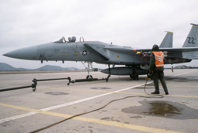 AN F-15 Eagle aircraft is refueled from a fuel bladder pit as a ground crewman talks to a pilot, aboard, on radio. The aircraft, from the 18th Tactical Fighter Wing, is involved in exercise Team Spirit '81