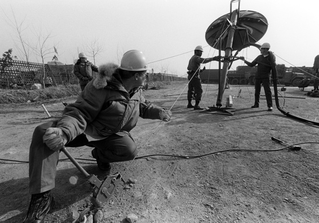 Combat communications group members erect a parabolic TRC-97A radio antenna during exercise Team Spirit '81