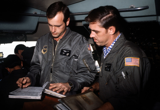CPT Dano Kinzie and TSGT Richard Brooks use a flight log to check the weight and balance of a C-141 Starlifter aircraft loaded with troops and cargo during exercise Team Spirit (Coronet Spray)