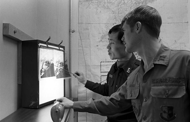 CPT Gerry Griggs and 1LT Kim Huyoung Ju look over a weather satellite photo. The men are from the Detachment 15, 30th Weather Squadron, involved in Exercise Team Spirit '81