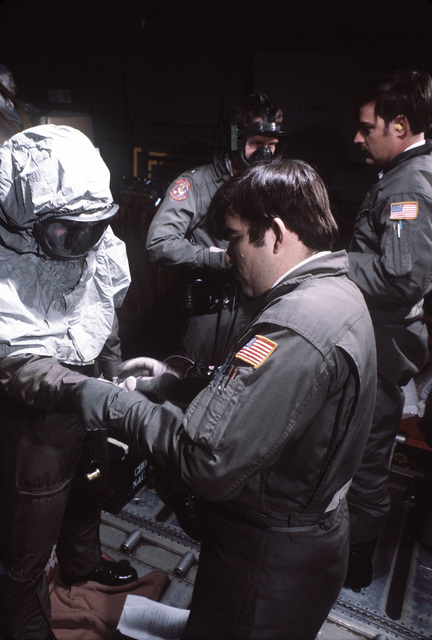Crewman aboard a C-141 Starlifter aircraft put on protective clothing during a chemical warfare exercise. The aircraft is en route from Dover, Delaware, to Germany