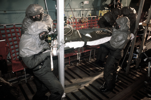 """Crewmen transfer a """"patient"""" onto a C-141 Starlifter aircraft during a chemical warfare exercise. All participants are wearing protective clothing"""