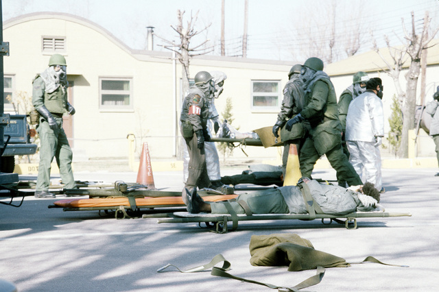 "Disaster preparedness team members wearing chemical warfare gear prepare ""litter patients"" for transportation to a medical center. The team is assigned to the 8th Combat Support Group, involved in exercise Team Spirit '81"