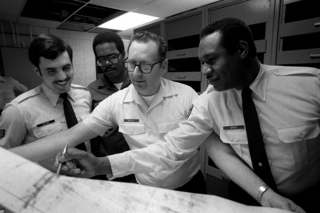 From right, CHIEF MSGT Rufus Gray, TSGT Larry G. Wright, SSGT Joseph Sessions and TSGT Jack Potter, from the 2044th Communication Group (2044th Comm. Gp.), review a plans and programs schematic for patch service at the Pentagon. The 2044th Communication Group is the recipient of the 1980 MGEN Harold M. McClelland Award