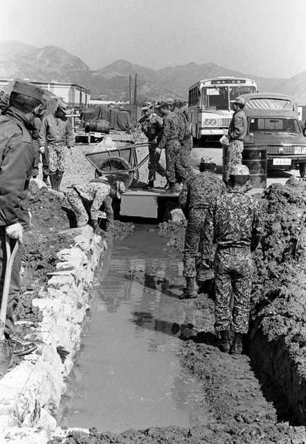 Korean Air Force members build a drainage ditch in the tent city during exercise Team Spirit '81