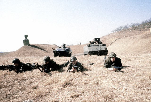 Korean and United States Air Force security policemen, followed by armored vehicles, participate in joint maneuvers during exercise Team Spirit '81