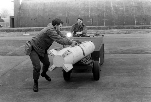 Loading crew supervisor SSGT Ron Lowery and SSGT Otto, left to right, use a bomb loader to carry an Mark 20 Rockeye bomb to an F-4 Phantom II aircraft for loading