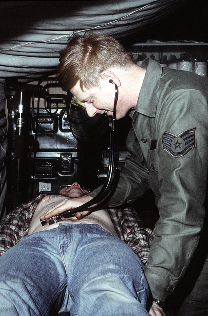 Medical SPECIALIST SSGT Herbert E. Sirman works on a patient in a tent emergency room. The airman is a 655th Tactical Field Hospital Squadron member involved in exercise Team Spirit '81