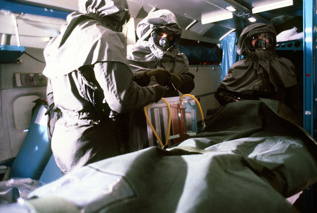"""Medical technicians and doctors work with """"patients"""" suffering various conditions during a chemical warfare training exercise. Personnel taking part in the exercise are wearing protective clothing"""