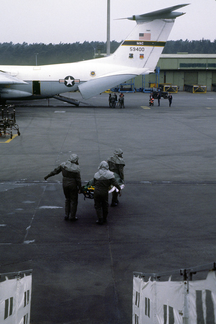 Medical technicians offload simulated patients from a C-9 Nightingale aircraft and carry them to a C-141 Starlifter aircraft. The men, wearing protective clothing, are participants in a chemical warfare training exercise