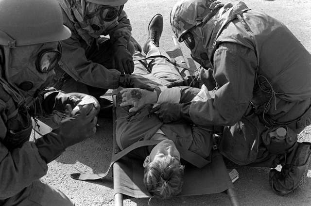 "Medics, wearing chemical warfare gear, attend a ""victim"" during base defense training, part of exercise Team Spirit '81"