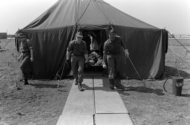 """Members of the 1ST Aeromedical Evacuation Squadron carry a """"patient"""" out of a tent city during exercise Team Spirit '81"""