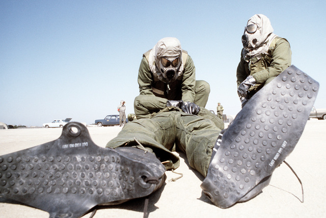 "Members of the 8th Combat Support Group disaster preparedness team, wearing chemical warfare gear, work on a ""casualty"" during exercise Team Spirit '81"