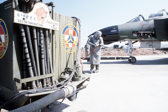 Members of the 8th Security Police Squadron, clad in chemical warfare gear, prepare to perform F-4 Phantom II aircraft decontamination maintenance during exercise Team Spirit '81