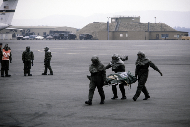 Patients are downloaded from a C-9 Nightingale aircraft and loaded onto a C-141 Starlifter aircraft during a chemical warfare exercise. All participants in the exercise are wearing protective clothing