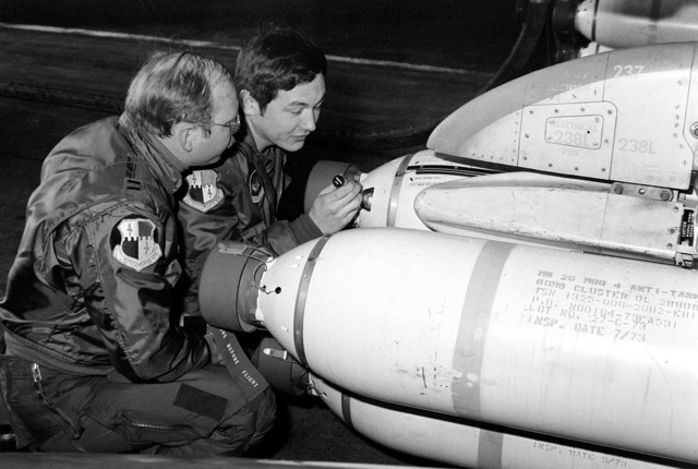 Pilots check Mark 339 fuse settings on Mark 20 Rockeye bombs loaded on an F-4 Phantom II aircraft. The pilots are members of the 52nd Tactical Fighter Wing, preparing for flight