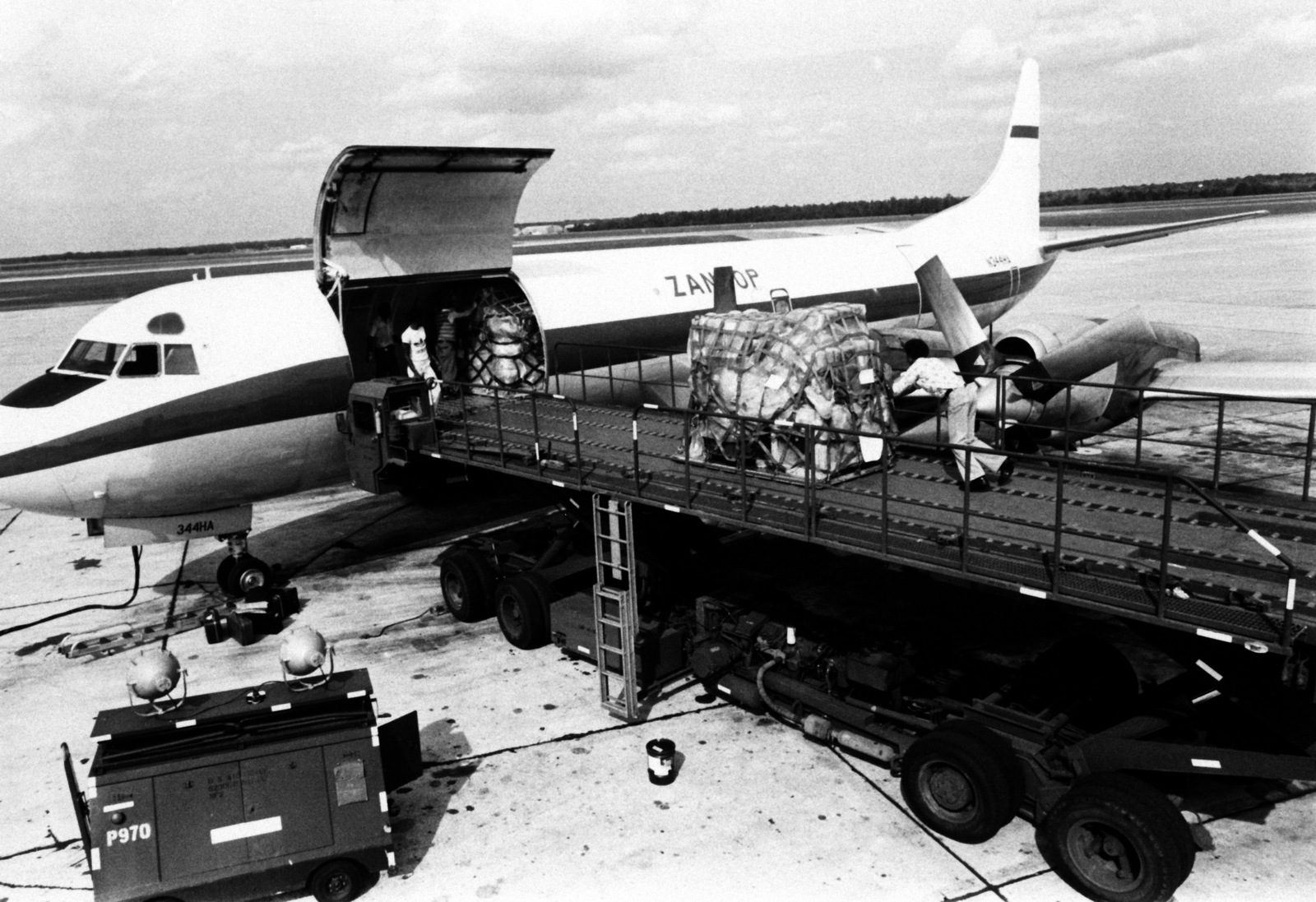 Priority cargo is loaded aboard an Electra aircraft from Zantop airlines, for delivery to a military installation. The aircraft is part of an air-cargo system called Log Air, operated by private airlines under contract to the Air Force